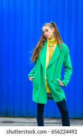 a young girl dressed in a green coat and yellow dress. Pure colors in the photo. girl fun fooling around . against the background of blue wall to show emotions