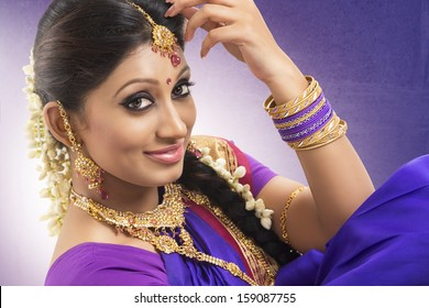 Young girl dressed in purple silk sari with jewels.
