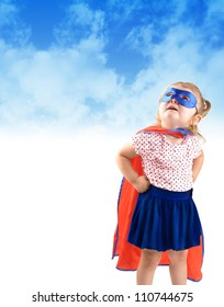 A young girl is dressed up as a superhero and looking up in the sky with a mask and cape. There is a copyspace to add a message area. Use it for a strength or halloween concept.