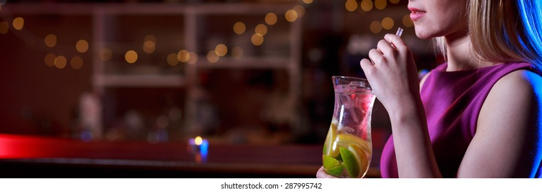 Young girl is drinking delicious coctail in the bar