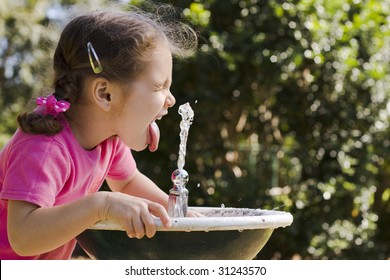 Young girl drinking at fountain