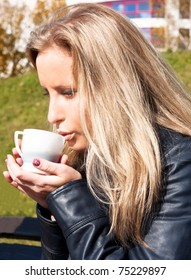 Young girl drinking hot tea in the park