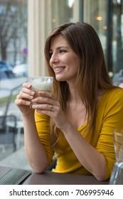 young girl drinking latte macchiatto in a coffee shop