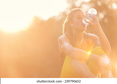 Young girl drinking water after workout