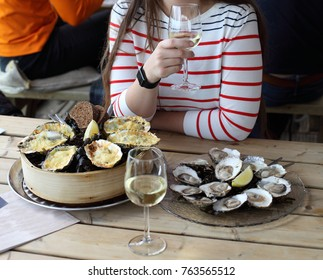 Young girl drinks  chardonnay wine and eats oysters in the restaurant on the oyster farm in the Yerseke, the Netherlands. Baked and raw oysters