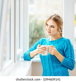 The young girl drinks tea and looks out the window. Square. The concept of lifestyle, autumn and comfort.