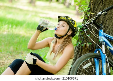 young girl drinks water from a bottle after mountain biking
