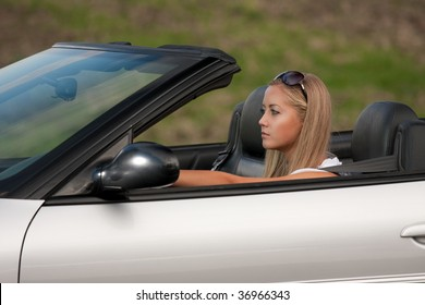 young girl driving cabrio car, on sunset light