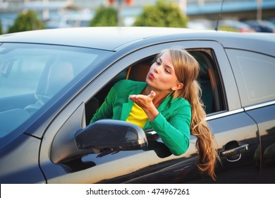 Young girl was driving the car. Business Woman in a jacket sends an air kiss. A successful and positive.