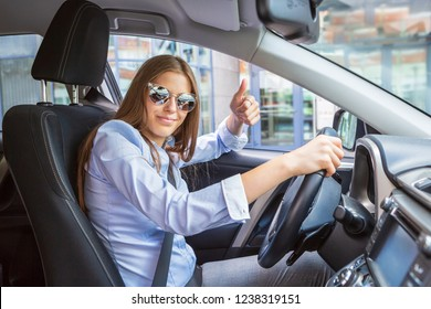 a young girl driving a car in the town