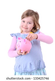 young girl dropping money into a pink piggy bank isolated on white background