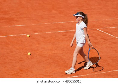 Young girl during tennis trainning on a clay