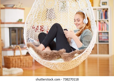 Young girl with earphone and smart phone in a Hanging chair
