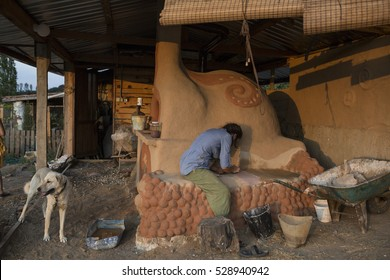 Young girl earth plastering the mud oven.