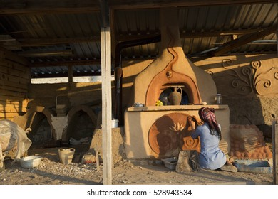 Young girl earth plastering the mud oven at the sunset.
