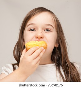 A young girl is eating a donut.  He is enjoying eating unhealthy food.