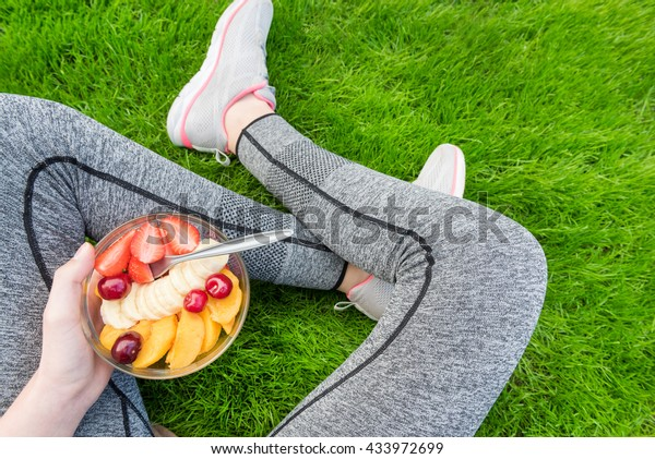 Young girl eating a fruit salad after a workout . Fitness and healthy lifestyle concept.