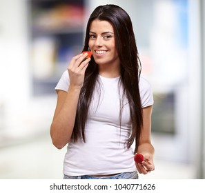 Young Girl Eating And Holding Strawberry, Indoor