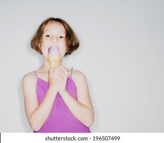 A young girl eating an ice cream cone.