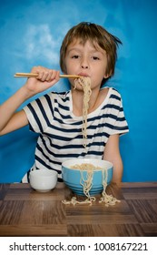 A young girl is eating noodles and making a real big mess