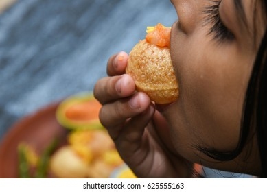 Young girl eating spicy Pani puri golgappe served with yogurt, Chat item, India. snacks eaten with tangy tamarind water and potato stuffing. Kid enjoying North Indian street food Delhi, Mumbai.