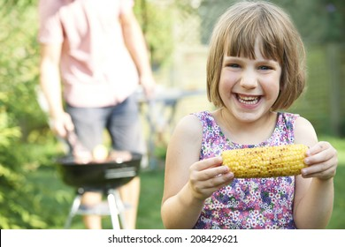 Young Girl Eating Sweetcorn At Family Barbe que