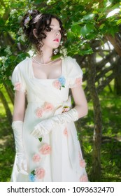 Young girl in an elegant long white bride dress near blooming bush in a spring garden.