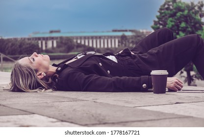 Young girl, elegantly dressed, sleeping outside in the open air, leaning on the floor next to her coffee. Business Woman / Student Concept.