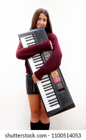Young girl embraces her musical keyboard