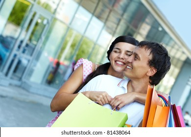 Young girl embracing her boyfriend with shopping bags