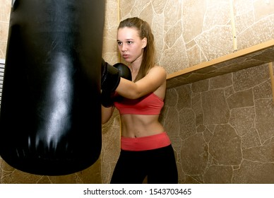 A young girl is engaged in boxing. Boxing training.Girl in boxing gloves.
