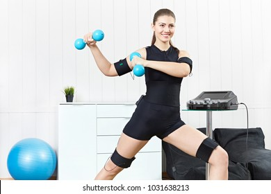 A young girl is engaged in fitness with blue dumbbells on the electric muscle stimulation machine. EMC training.