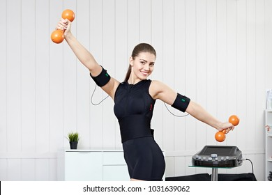 A young girl is engaged in fitness with orange dumbbells on the electric muscle stimulation machine. EMS training.