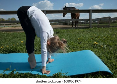 The young girl is engaged in gymnastics on the grass healthy lifestyle. Child girl doing gymnastics. Little cute girl practicing yoga pose on the background of the paddock with a horse