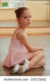 Young girl engaged in a pink ballet tutu and pointe in the ballet hall on the wooden dance floor