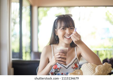 Young girl enjoy her drinking cold cocoa drink in the bakery shop