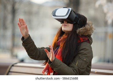 Young girl enjoy playing with cool new virtual reality glasses for mobile gaming applications.Use mobile apps with innovative virtual technology.Augmented reality gamer gadget.Woman play on vr headset