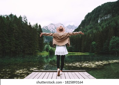 Young girl enjoying beauty of nature looking at mountain lake in Jezersko. Adventure travel in Slovenia, Europe. Woman stands with raised arms on wooden bridge on background with forest and Alps.