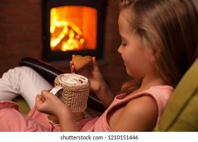 Young girl enjoying a cookie with a hot chocolate sitting by the fireplace - relaxing in the holidays season