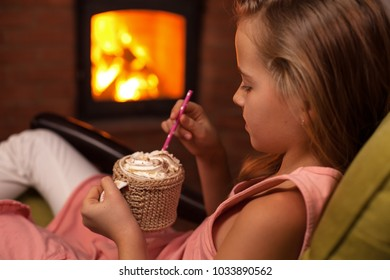 Young girl enjoying a hot chocolate with whipped cream in front of the fireplace in winter or holidays season, shallow depth