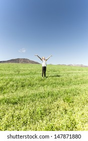 Young girl enjoying life on a summer day in a beautiful grassy meadow