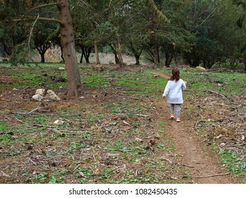 Young girl with enjoying nature and the outdoors walking in the forest back to camera
