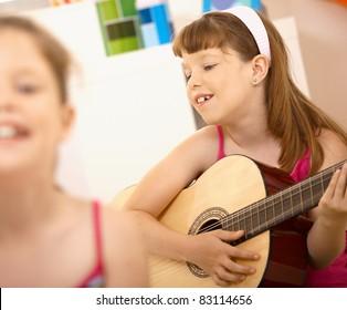 Young girl enjoying playing guitar, smiling at home.?