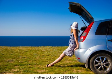young girl enjoying the sea view sitting on the trunk of the car