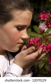 young girl enjoying the smell of a pink flower