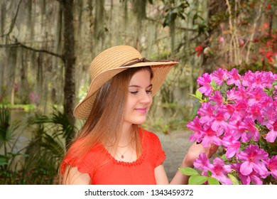 Young girl  enjoying time in the beautiful blooming  garden. Azaleas in bloom in the  park with trees with spanish moss. Magnolia Plantation and Gardens, Charleston, South Carolina, USA