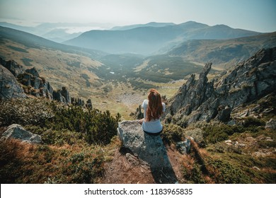 Young girl enjoying a view from the top of Carpathian mountain. Relaxing alone with nature