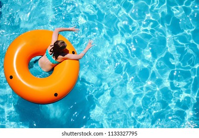 A young girl enjoys a refreshing float in the swimming pool.