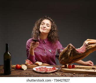 Young girl enjoys the taste of a jamon and wine