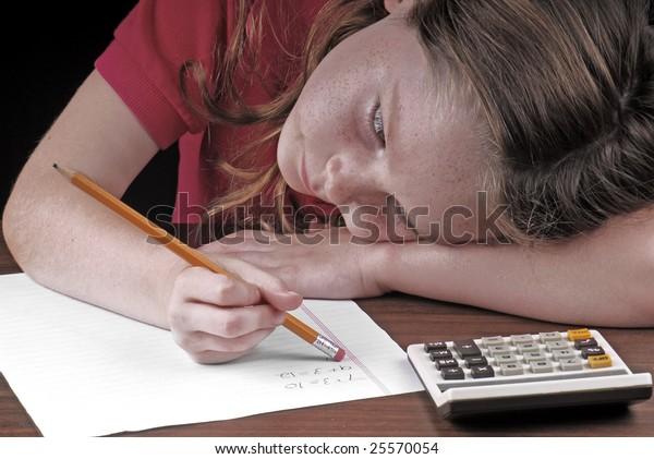 young girl erasing mistake on math homework